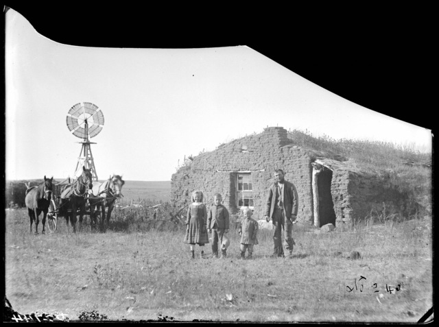 Man and three children in front of Con Fleshman sod house, Dale Valley, Nebraska.