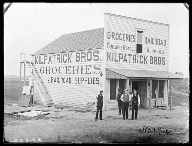 Men in front of Kilpatrick Bros. Groceries & Railroad Supplies store, Broken Bow, Nebraska