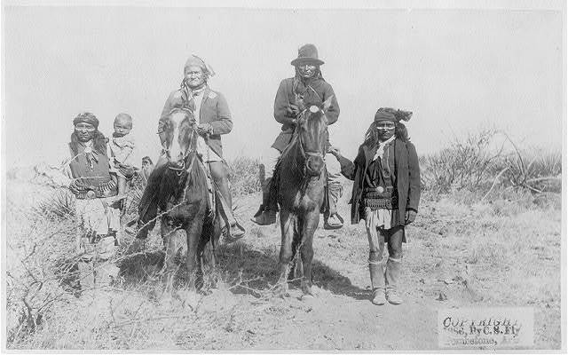 [Scene in Geronimo's camp...before surrender to General Crook, March 27, 1886: Geronimo and Natches mounted; Geronimo's son (Perico) standing at his side holding baby]