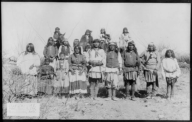 [Scene in Geronimo's camp...before surrender to General Crook, March 27, 1886: group of 18 men, women and children]