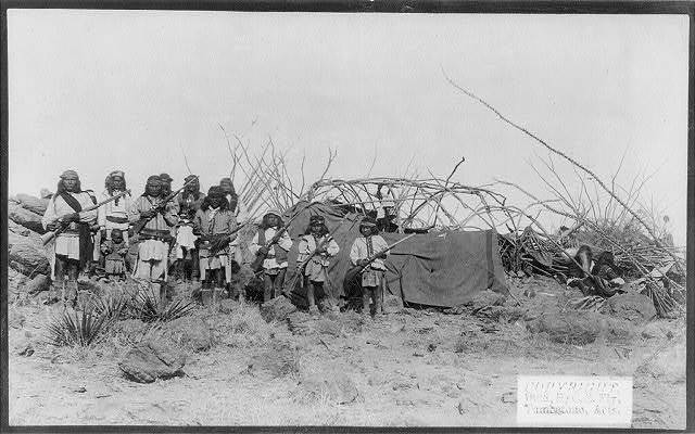 [Scene in Geronimo's camp...before surrender to General Crook, March 27, 1886: group in Natches' camp; boys with rifles]
