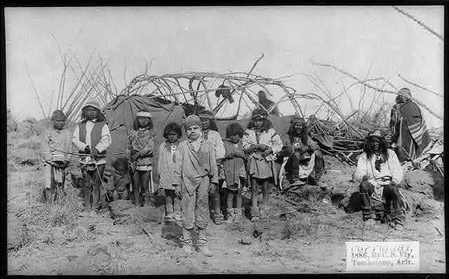 [The captive white boy, Santiago McKinn in Geronimo's Camp, with group of Indians, mostly children, in front of partially constructed tent, before Geronimo's surrender to Gen. Crook, March 27, 1886]