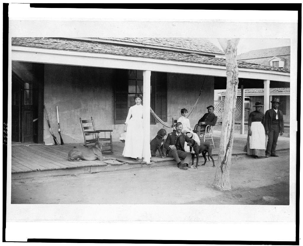 [Two soldiers and two women on porch, with Afro-American woman and man to right, Fort Verde, Arizona]