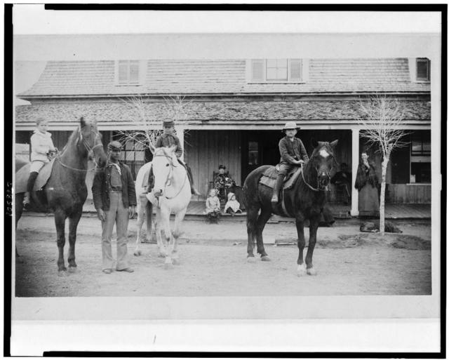 [Afro-American enlisted man standing by three officers' children on horseback, Fort Verde, Arizona]