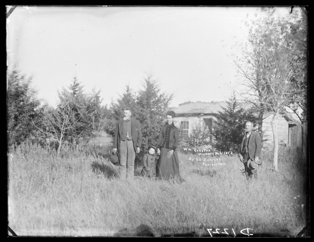 Capt. and Mrs. William H. Comstock (standing left) in front of their log house near Westcott, Custer County, Nebraska
