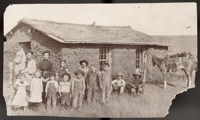 Family in front of a sod house, probably in Custer County, Nebraska