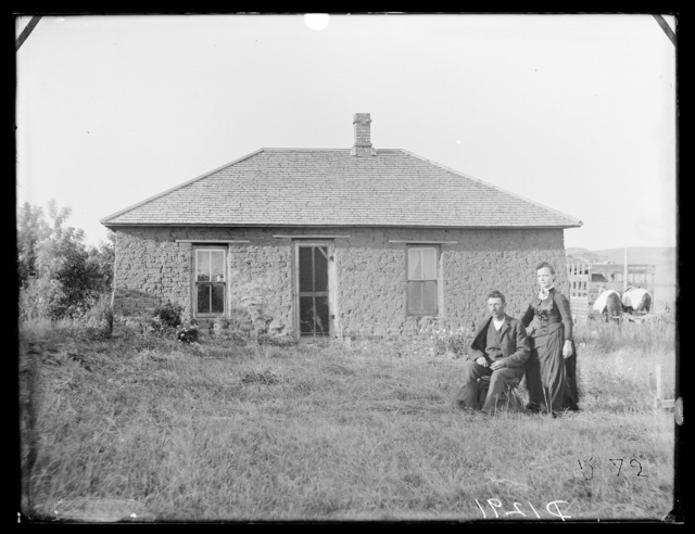 Mr. & Mrs. Philip W. Lynch in front of their sod house which Mr. Lynch built, Custer County, Nebraska.
