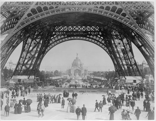 Paris Exposition, view from ground level of the Eiffel tower with Parisians promenading
