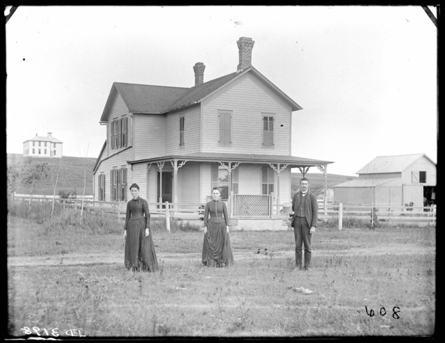 A man, woman, and younger woman in front of farmhouse in east Custer County, Nebraska.