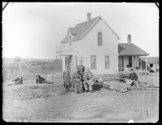 Family in front of a frame farmhouse in southeastern part of Custer County, Nebraska.