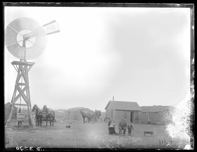Family in front of a small frame house between two sod buildings, Custer County, Nebraska.