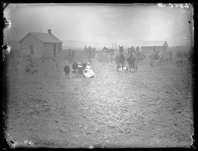 Family in front of a small one-story frame house near Broken Bow, Custer County, Nebraska.