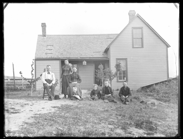 Family in front of frame farmhouse in eastern part of Custer County, Nebraska.