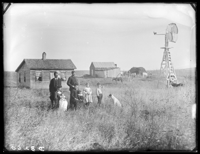 Family in front of small one-story frame house in northern part of Custer County, Nebraska.
