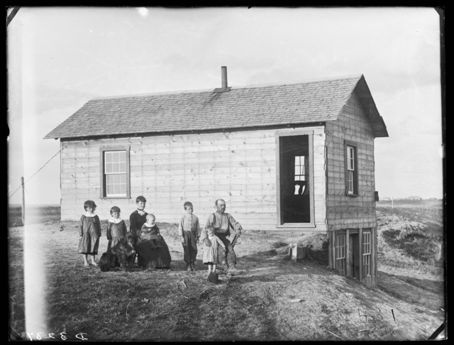 Family in front of the frame house of Mr. Wells in eastern part of Custer County, Nebraska.