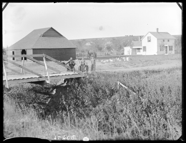 Family standing near a new wooden bridge; frame house and large barn in Custer County, Nebraska
