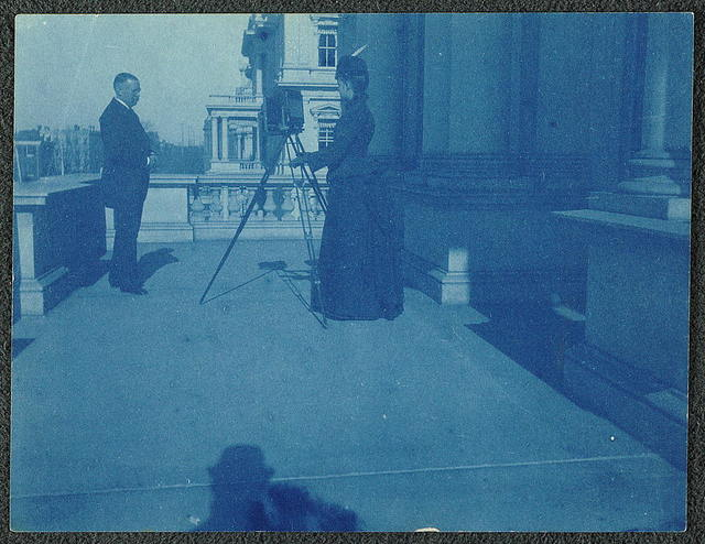 [Frances Benjamin Johnston on a balcony of the State, War and Navy Building with a tripod-mounted camera, photographing an unidentified man]
