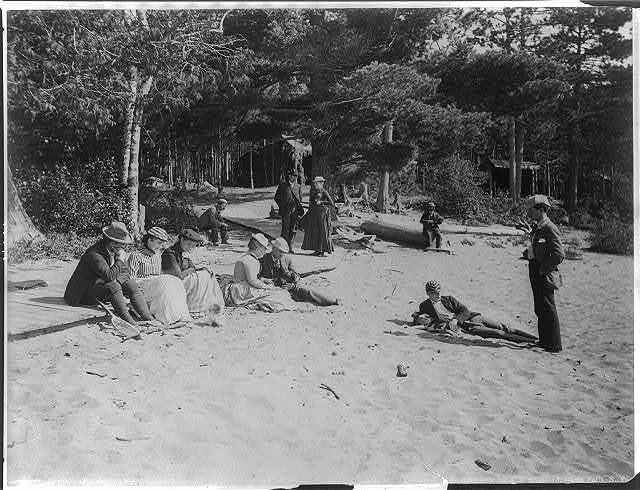 [People relaxing on sandy beach in the Adirondack Mts., N.Y.; lean-tos in backgrd.