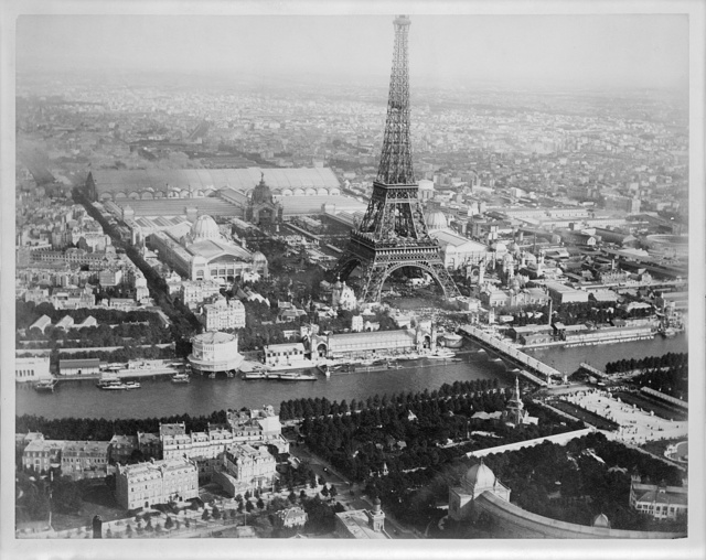 [Aerial view of Paris, France, from a balloon, showing the Seine River and the Eiffel Tower at center, and buildings of the Exposition universelle]