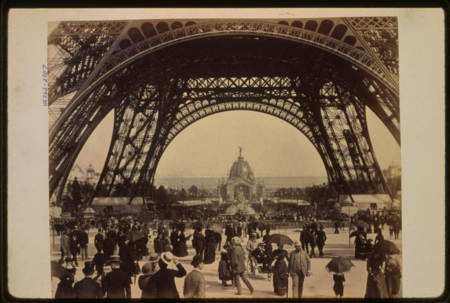[Crowd of people walking under the base of Eiffel Tower, view toward the Central Dome, Paris Exposition, 1889]