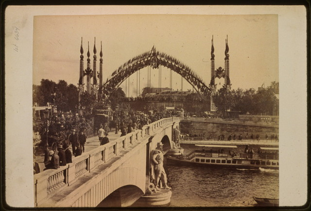 [Crowds crossing the Pont de l'Alma, looking toward the Passerelle de l'Alma on the Quay d'Orsay, Paris Exposition, 1889]