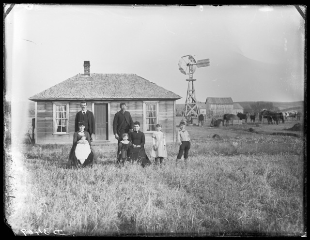 Family in front of a one-story frame house in Custer County, Nebraska.