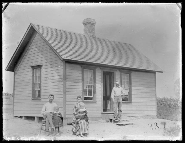 Family in front of frame farmhouse in Custer County, Nebraska.