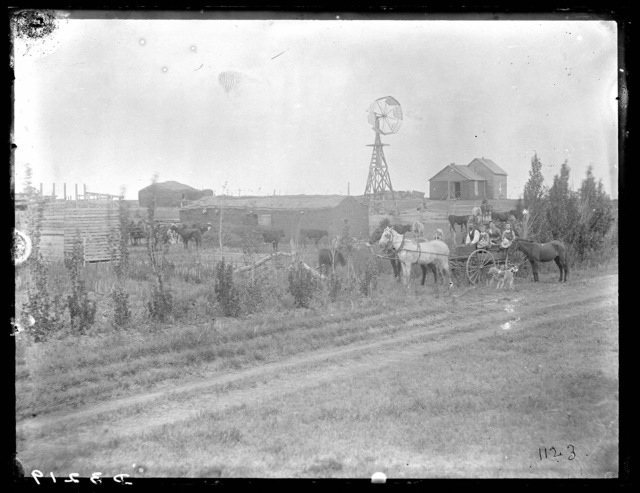 Family shown in horse-drawn wagon in farm scene, northwestern part of Custer County, Nebraska.
