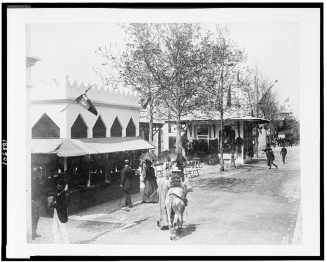 """[Girl riding donkey in front of the Pavilions of Morocco on """"a street in Cairo"""", Paris Exposition, 1889]"""