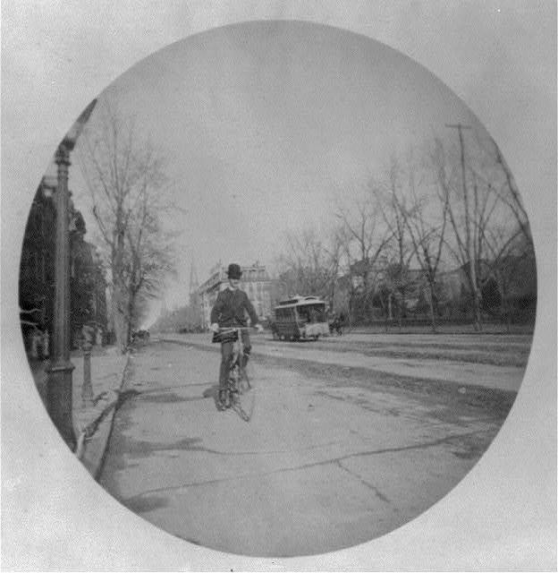 [Man on bicycle on street, Washington, D.C., with horse-drawn streecar in background]