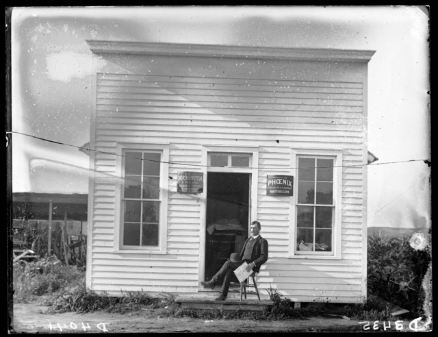 Man seated on chair in front of insurance office at Sargent, Custer County, Nebraska.