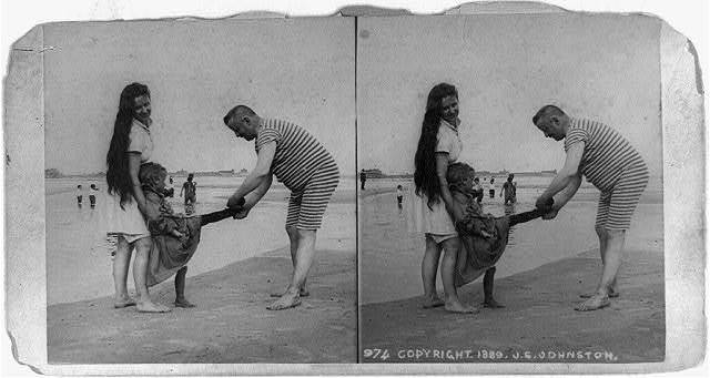 [Man, woman, and girl in foreground on beach, with man holding girl's foot]