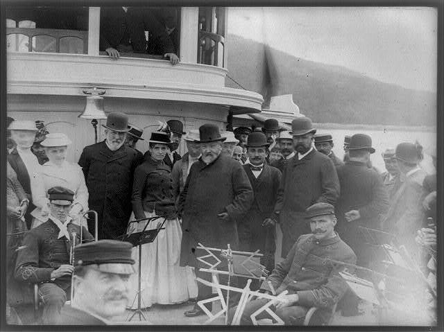 [President Benjamin Harrison with James G. Blaine, Secretary of State, Henry Cabot Lodge, and group of other people posed, possibly on the forward deck of the Frenchman's Bay steamer Sappho, with several men of the Bar Harbor Band, Maine(?)]