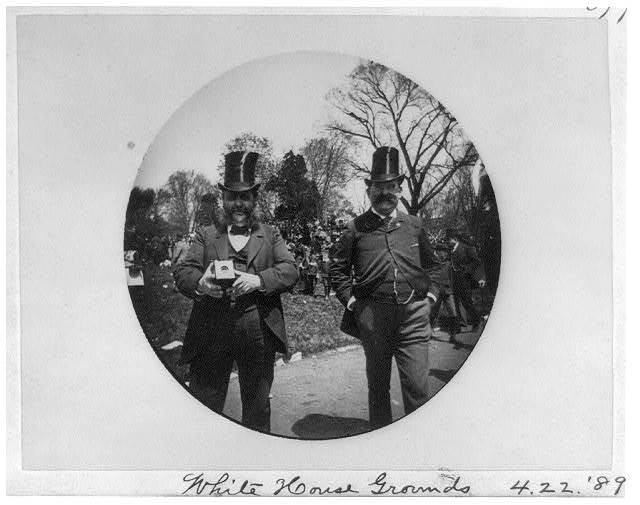 [Two men in high silk hats, one with Kodak camera, on the White House grounds, Washington, D.C.]