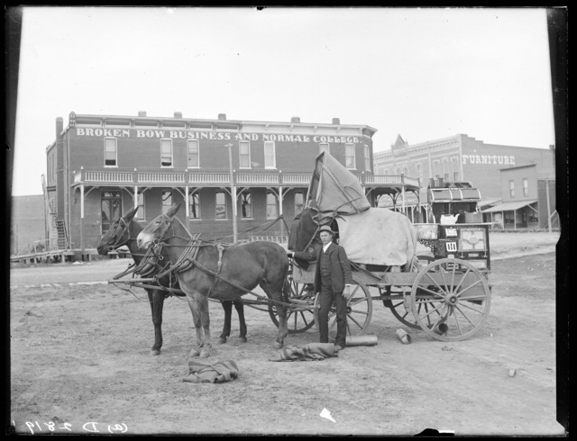 A dray wagon hauling a new stove in front of the Broken Bow Business and Normal College