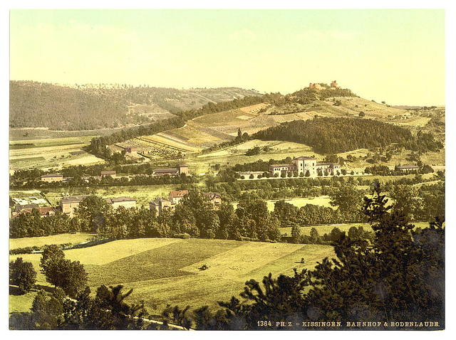 [Bad Kissengen (i.e. Bad Kissingen) railway station and the Bodenlaube, seen from the Altenberg, Bavaria, Germany]