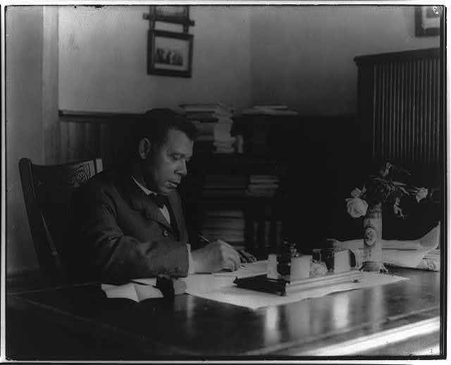 [Booker T. Washington, half-length portrait, seated at desk, facing right]