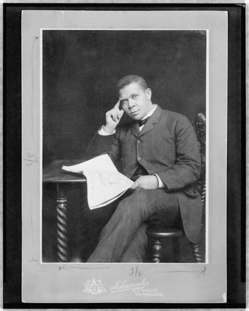 [Booker T. Washington, three-quarter length portrait, seated, facing slightly left, holding newspaper]