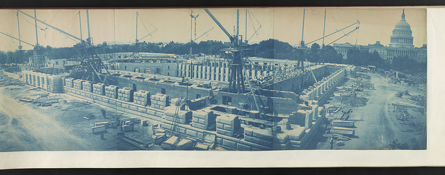 [Builders at work on the rusticated stone walls of the Library of Congress Thomas Jefferson Building during its construction; U.S. Capitol in the background]
