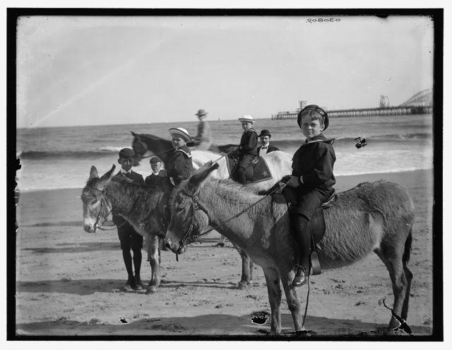 [Children riding donkeys at a beach]