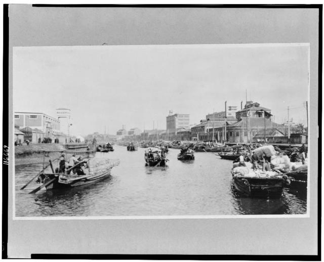 China, Kiangsu Province, Shanghai, industrial plants on Soochow Creek, with boats at a cotton mill in the foreground