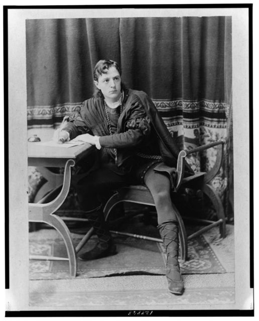[Creston Clarke, full-length portrait, facing slightly right, seated at desk, writing with quill pen, as a character in a play]