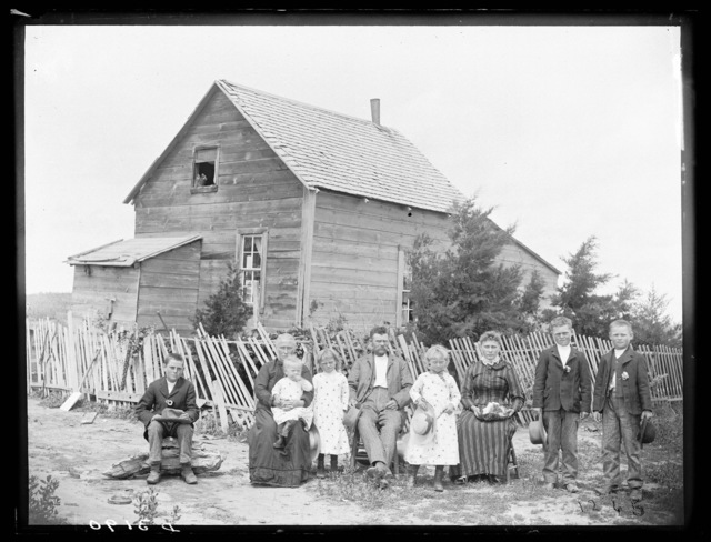 Family in front of a farmhouse in southwest Custer County, Nebraska.