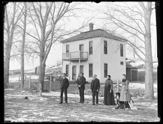 Family in front of two-story farmhouse near Westerville, Nebraska.