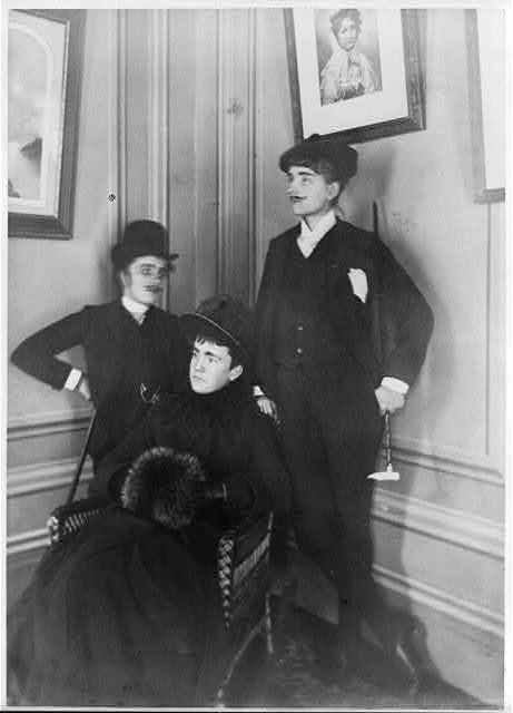 [Frances Benjamin Johnston, full lgth., standing, in costume, wearing mustache, posed with 2 other people]
