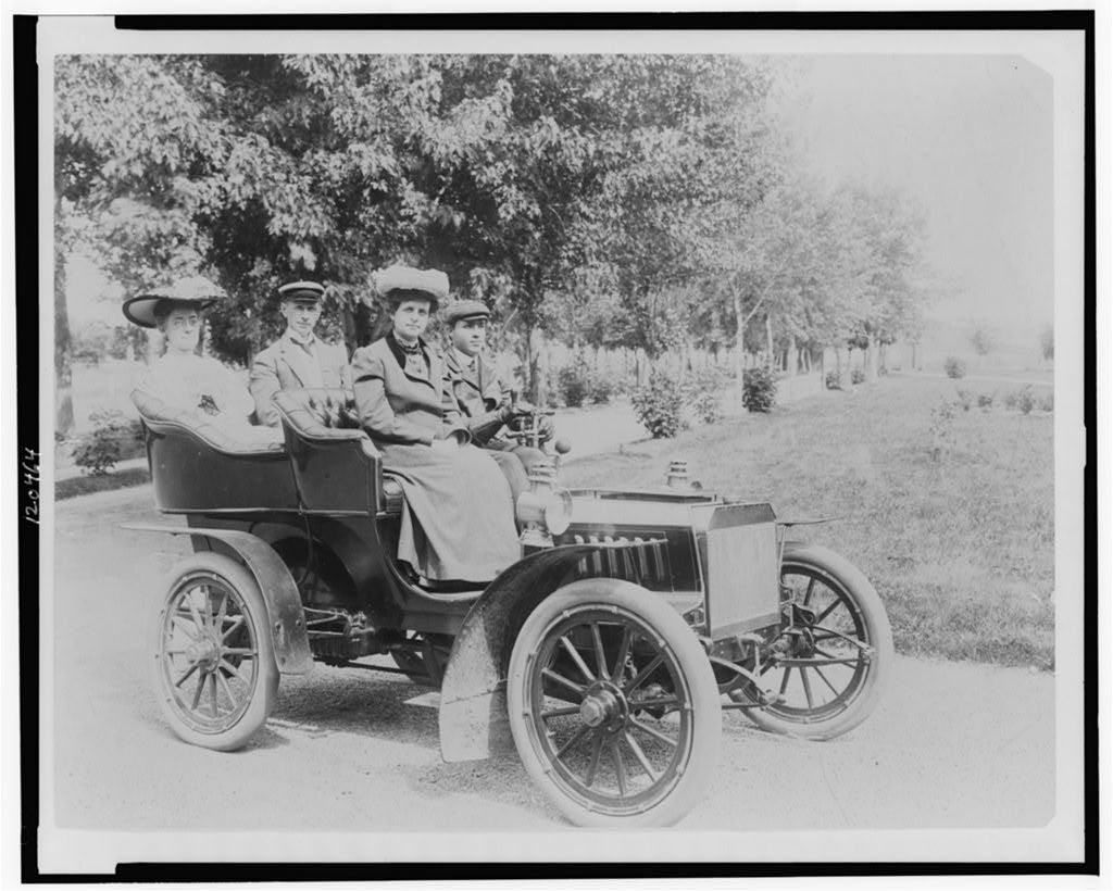 [Frances Benjamin Johnston seated with three other people in automobile]