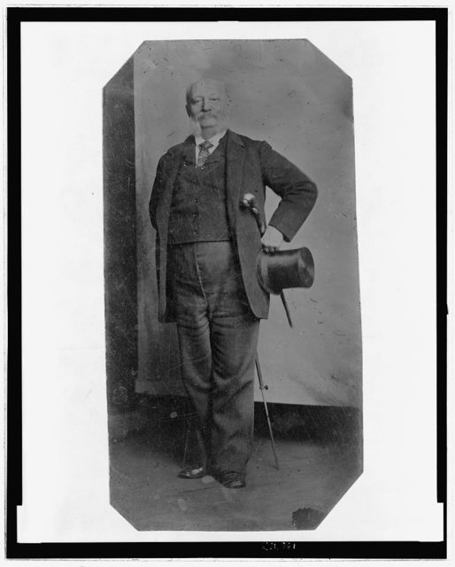 [Full-length portrait of a man holding a top hat and walking stick]