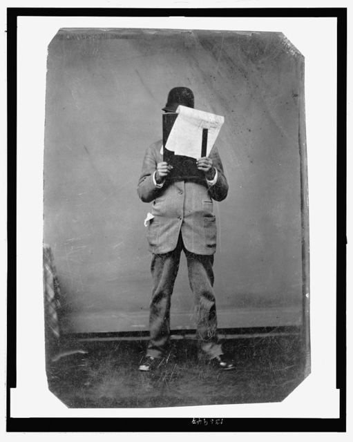 [Full-length portrait of a man in suit and hat, holding papers and a board(?) in front of his face while cluthching a ruler(?)]