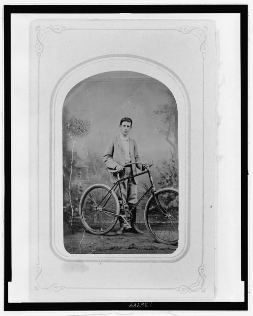 [Full-length portrait of a young man standing next to a bicycle]