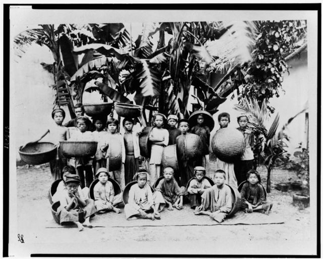 [Group of children, with baskets, posed under palm tree, Saigon, South Vietnam]